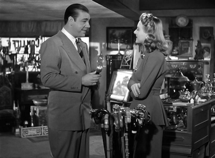 The Wolf Man (Larry Talbot) and Gwen Conliffe discuss walking sticks in her antique shop.